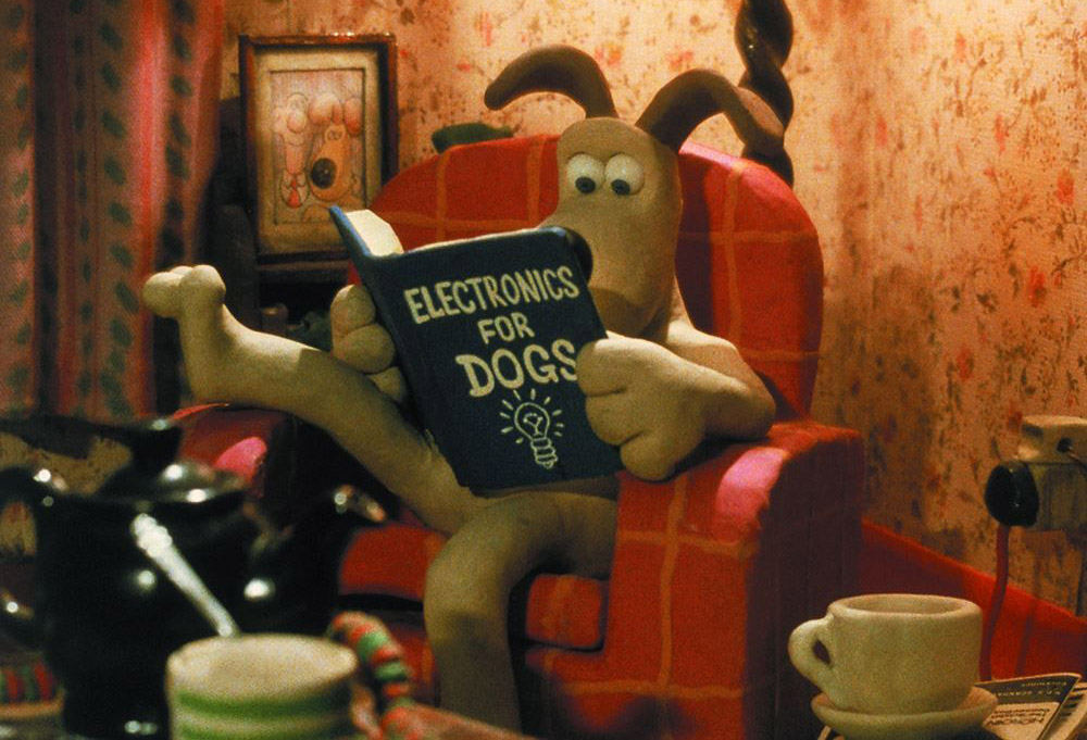 A frame from the cartoon Wallace and Gromit. Gromit reads the book Electronics for dogs
